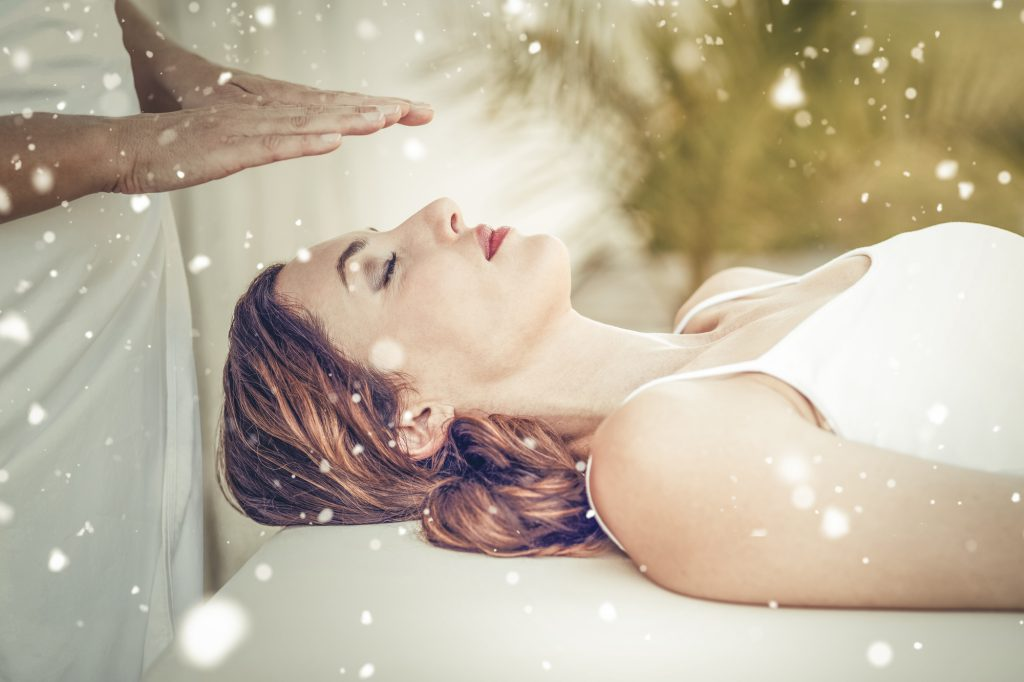 Snow against calm woman receiving reiki treatment